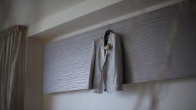 Ett omslag för glack för man` som s hänger i sovrummet, hänger på en hängare för bröllopet för brudgum` s lager videofilmer