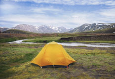 Ett orange tält på en flodkust Royaltyfria Bilder