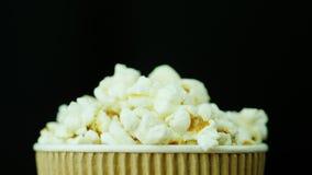 Ett pappers- exponeringsglas av popcorn, roterar långsamt och slätt på en svart bakgrund royaltyfri fotografi