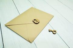 Ett pappers- postkuvert är stängt med ett lås bredvid tangenten på en vit tabell, en hemlighet royaltyfri foto