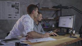 Ett par av anställda diskuterar den arkitektoniska orienteringen på datoren, nära på tabellen är ritningarna arkivfilmer