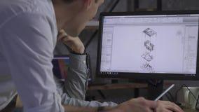 Ett par av arkitekter sitter framme av datoren och diskuterar en byggnadsteckning arkivfilmer