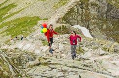 Ett par av att le turister med trekking klibbar på slingan i bergen Mannen med ryggsäcken har hakat uppblåst ballo Royaltyfri Foto