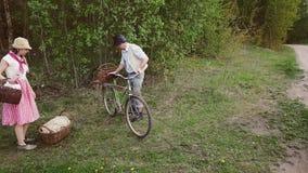 Ett par av bönder tar en gammal cykel i skogen stock video