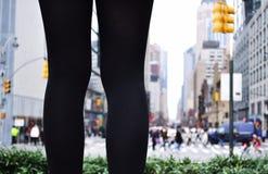 Ett par av ben som står i en stad royaltyfria foton
