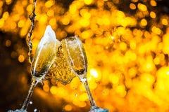 Ett par av champagneflöjter med guld- bubblor gör jubel på guld- ljus bakgrund med utrymme för text Fotografering för Bildbyråer