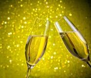 Ett par av champagneflöjter med guld- bubblor på bokehbakgrund för gult ljus Royaltyfri Bild