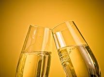 Ett par av champagneflöjter med guld- bubblor på guld- ljus bakgrund Arkivbilder