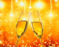 Ett par av champagneflöjter med guld- bubblor på guld- stjärnor tänder bakgrund Royaltyfri Foto
