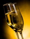Ett par av champagneflöjter med guld- bubblor på mörk guld- ljus bakgrund Fotografering för Bildbyråer