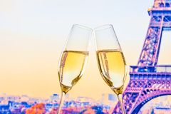 Ett par av champagneflöjter med guld- bubblor på suddighet står högt Eiffel bakgrund Royaltyfri Fotografi