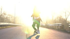 Ett par av dansare utför ett synkroniseringsbaletthopp på gryning, läckor långsam rörelse stock video