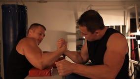 Ett par av den muskulösa mannen som mäter styrkor Armwrestling arkivfilmer