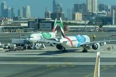 Ett par av Emirates Airlines flygplan med logoer för expo 2020 De parkerar på den Dubai International flygplatsen royaltyfria bilder