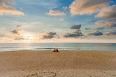 Ett par av ensamt turist- sammanträde på stranden på Phuket royaltyfria bilder