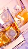 Ett par av exponeringsglas av whisky med is på diskoviolet tänder Royaltyfri Foto