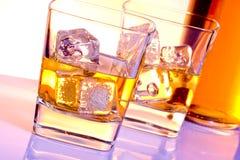Ett par av exponeringsglas av whisky med is på diskoviolet tänder Royaltyfri Bild
