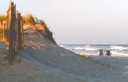 Ett par av folk som kopplar av på en strand royaltyfri bild