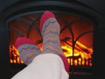 Ett par av fot och en hemtrevlig brand Arkivfoto