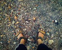 Ett par av fot som bär bruna sandaler på de kulöra mycket lilla stenarna som en bakgrund royaltyfria bilder