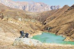 Ett par av gammalt piskar tappningskor står på en sten mot bakgrunden av en bergturkossjö, och epos vaggar royaltyfri bild
