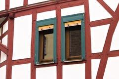 Ett par av gröna fönster av en korsvirkes- husTyskland royaltyfri bild