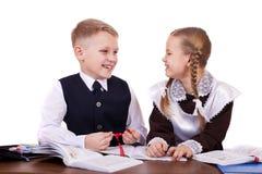 Ett par av grundskolastudenter sitter på ett skrivbord Royaltyfri Fotografi