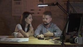 Ett par av kontorsarbetare arbetar sent i aftonen framme av datoren och att diskutera workflowen lager videofilmer