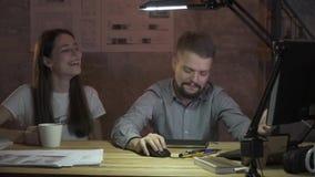 Ett par av kontorsarbetare sitter med kaffe som är främst av en dator och ett skratt som diskuterar arbete lager videofilmer