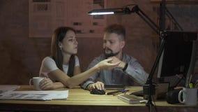 Ett par av kontorsarbetare sitter på en dator och ett arbete sent i aftonen som diskuterar ett arbetsplan arkivfilmer