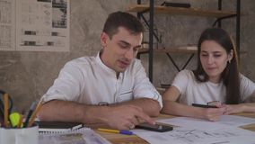 Ett par av kontorsarbetare som ser en teknisk uppgift för en teckning i telefonen arkivfilmer