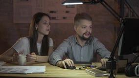 Ett par av kontorspersonalen som tillsammans arbetar på en dator som sent arbetar i aftonen lager videofilmer