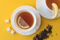 Ett par av kopp te med citronen och socker royaltyfria bilder