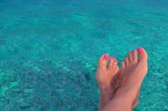 Ett par av kvinnliga ben på en bakgrund av blått vatten arkivfoton