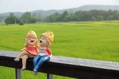 Ett par av modellen som tillsammans sitter i risfältet Arkivbild