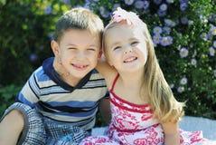 Ett par av pojken och flickan nära färgar Arkivfoton