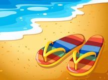 Ett par av sandaler på stranden Royaltyfria Bilder
