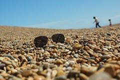 Ett par av solglasögon lägger på en singelstrand i Dorset, UK arkivbild