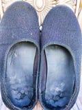 Ett par av svarta smutsiga skor royaltyfri fotografi