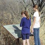 Ett par av systrar läser ett tecken på Murray Springs Clovis Site Arkivfoto