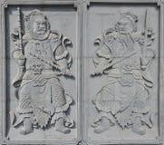 Ett par av tegelsten som snider dörr-guden Arkivbild