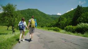 Ett par av turister med ryggsäckar rymmer händer och promenerar vägen i ett pittoreskt ställe isolated rear view white stock video