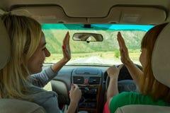 Ett par av två unga härliga flickor som reser med bilen i moen royaltyfri fotografi