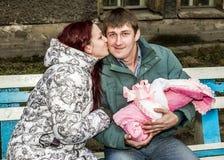 Ett par av unga föräldrar med behandla som ett barn att kyssa på bänken Royaltyfri Foto
