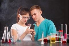 Ett par av unga kemister ser den svarta smartphonen Begreppet av vetenskap På en mörk bakgrund Fotografering för Bildbyråer