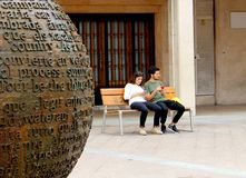 Ett par av ungdomarkontrollerar uppmärksamt deras mobiltelefoner royaltyfri bild
