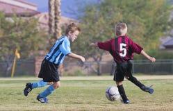 Ett par av ungdomfotbollspelare konkurrerar Arkivbild
