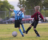 Ett par av ungdomfotbollspelare konkurrerar Arkivfoto