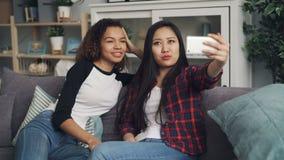 Ett par av vänner gör online-video appell med smartphoneinnehavapparaten och att se skärmen, samtal och att göra en gest arkivfilmer