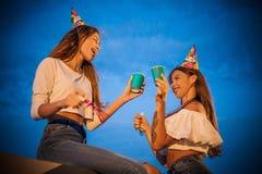 Ett par av vänner med visslingar och drinkar som firar deras födelsedag royaltyfria bilder